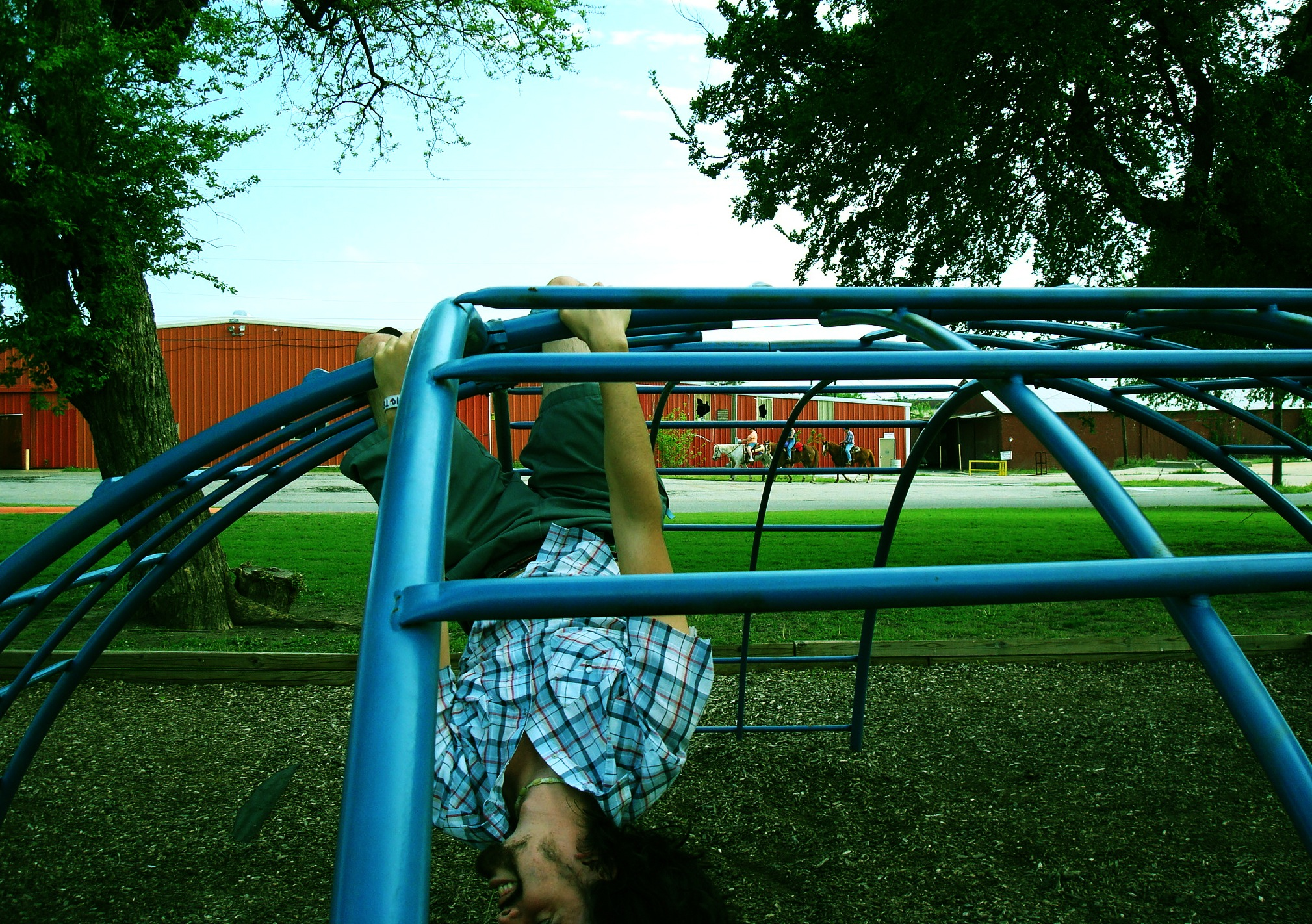 Daniel being Daniel, hanging upside-down from monkey bars